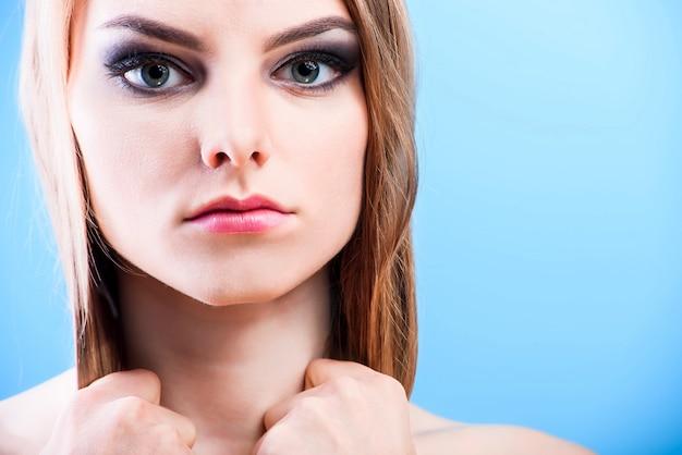 Portret van mooie vrouwelijke blonde model op blauwe achtergrond