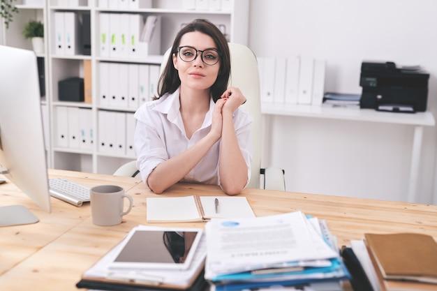 Portret van mooie vrouwelijke manager in glazen zit aan houten bureau met open dagboek in moderne kantoren