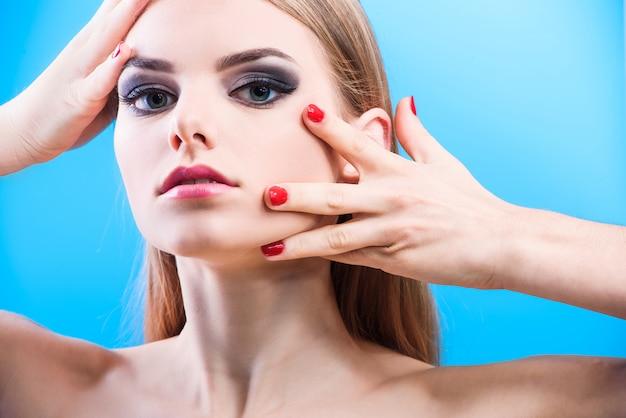 Portret van mooie vrouwelijke model op blauwe achtergrond