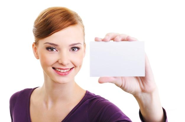 Portret van mooie vrouwelijke persoon met blanco visitekaartje in de hand.