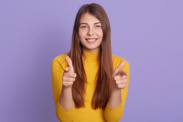 Portret van mooie vrouwelijke student met brede glimlach met gelukkige uitdrukking met beide handen, poseren geïsoleerd over lila muur.