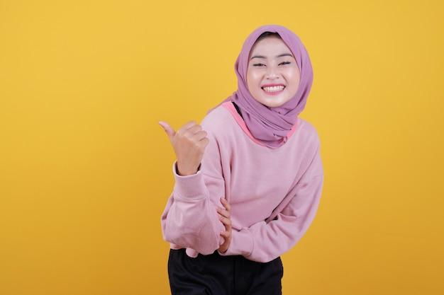 Portret van mooie vrouwelijke vrouw met brede glimlach en omhoog duimen