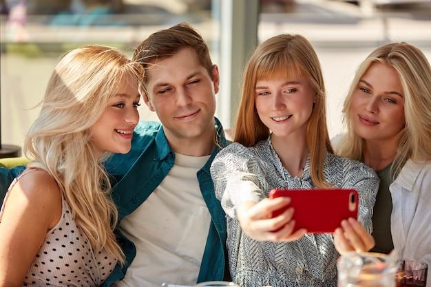 Portret van mooie vrouwen die foto op mobiele telefoon nemen