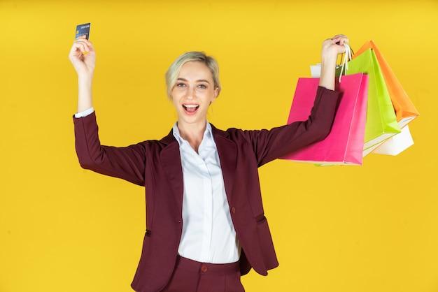 Portret van mooie vrouwen die het winkelen zakken met creditcard houden en genieten van winkelend op geel