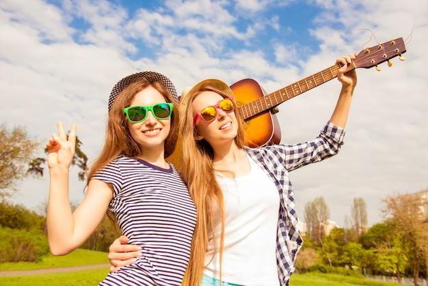 Portret van mooie vrouwen die in glazen gitaar in het park houden