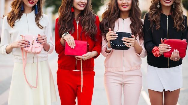 Portret van mooie vrouwen die in roze robes vrijgezellenfeest vieren.
