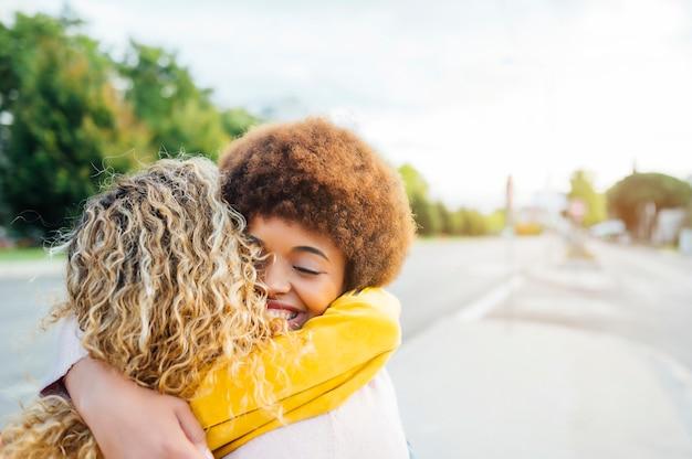 Portret van mooie vrouwen die ze knuffelen op straat. lgtb-concept