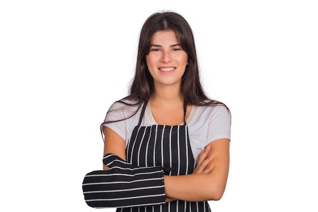 Portret van mooie vrouwenchef-kok die een gestreepte schort draagt en keukengerei in studio houdt.