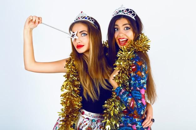 Portret van mooie vrouwenvrienden die heldere sexy outfits, grappige valse kronenklatergoud en magische behoefte dragen, klaar voor het vieren van vakantiefeest. samen lol hebben, schreeuwen en gekke bekken trekken.