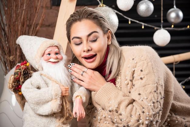 Portret van mooie vrouwenzitting met santa claus-stuk speelgoed hoge kwaliteitsfoto