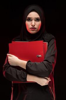 Portret van mooie wanhopige doen schrikken bang gemaakte jonge moslimvrouw die zwarte hijab holdingsomslagen dragen als het houden van geheim concept zwart