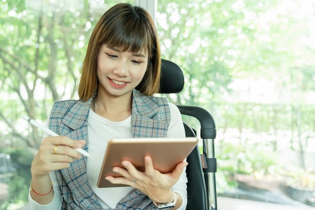 Portret van mooie werkende vrouw die tablet met slimme pen gebruikt