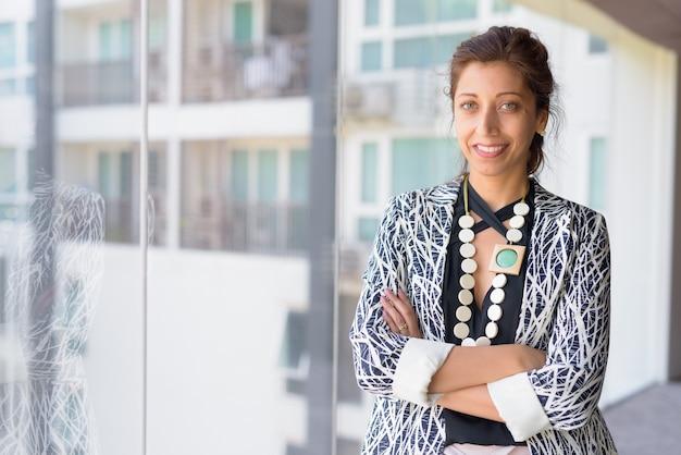 Portret van mooie zakenvrouw bij het glazen raam van het kantoorgebouw binnenshuis