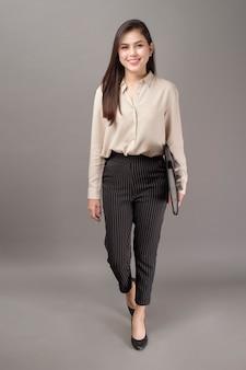 Portret van mooie zakenvrouw lacht op grijs