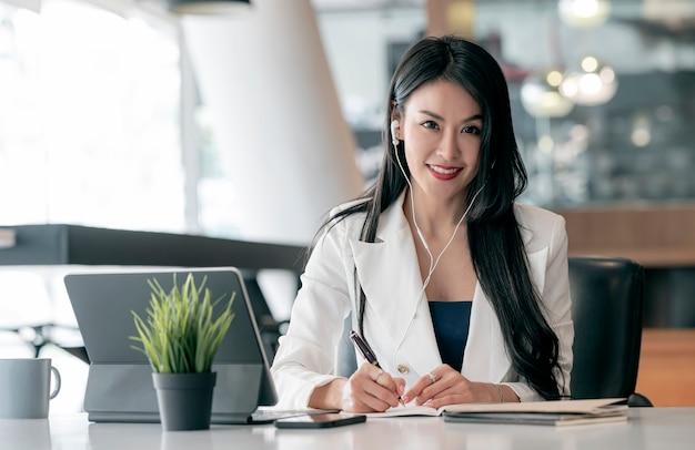 Portret van mooie zakenvrouw met oortelefoon met pen schrijven op notitieblok, glimlachend en camera kijken terwijl zittend aan haar bureau.