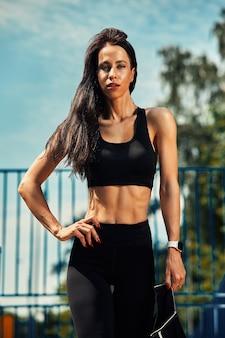 Portret van mooie zelfverzekerde vrouw op een sportveld close-up, leidt een gezonde levensstijl