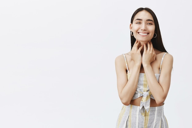 Portret van mooie zorgeloze en vrolijke vrouw die breed glimlacht na het zien van de resultaten van de cosmetologische procedure, het verzorgen van de huid over de grijze muur