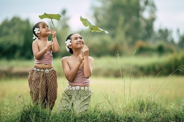 Portret van mooie zus en jonge zus in thaise traditionele kleding en witte bloem op haar oor gezet, kijkend naar lotusblad in de hand en glimlachen met gelukkig op rijstveld, kopieer ruimte