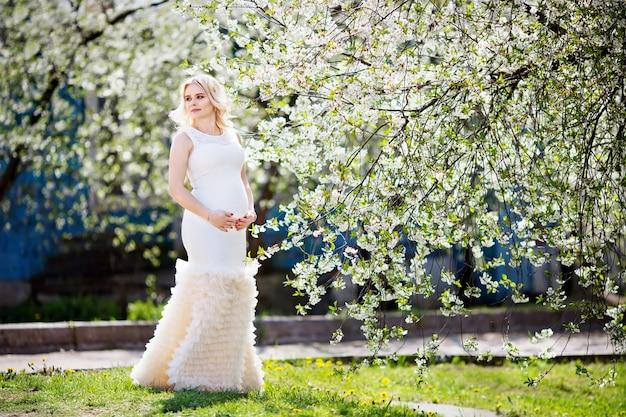 Portret van mooie zwangere vrouw in het bloeiende park. jonge gelukkige zwangere vrouw die van het leven in aard geniet.