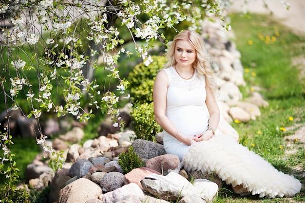Portret van mooie zwangere vrouw in het bloeiende park. jonge gelukkige zwangere vrouw ontspannen in de natuur.