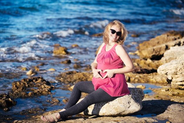 Portret van mooie zwangere vrouw op strand