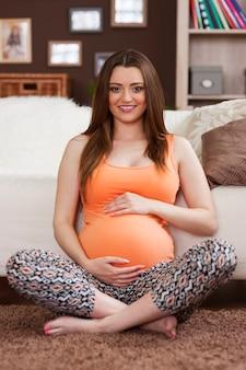 Portret van mooie zwangere vrouw thuis