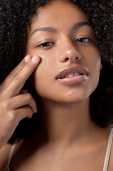 Portret van mooie zwarte vrouw die foundation aanbrengt