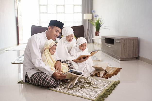 Portret van moslim en gelukkige familie met kinderen die koran lezen en thuis samen bidden