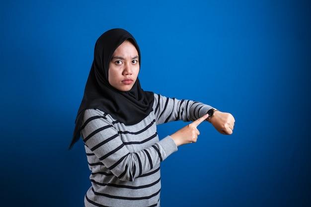 Portret van moslim student college meisje keek boos terwijl ze haar polshorloge liet zien, late tijd concept, geïsoleerd op blauwe achtergrond