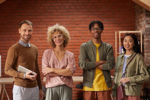 Portret van multi-etnisch creatief business team permanent met hun armen gekruist en glimlachend in de camera op kantoor