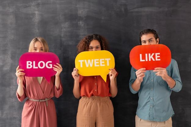 Portret van multi-etnische gebruikers van sociale media die monden bedekken met kleurrijke tags met activiteitswoorden van bloggers