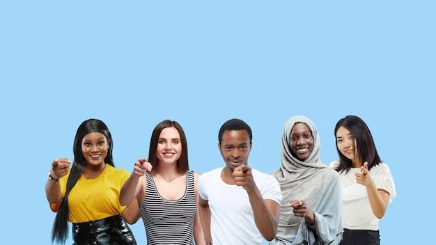 Portret van multi-etnische groep jongeren geïsoleerd op blauwe studio achtergrond, flyer, collage. concept van menselijke emoties, gezichtsuitdrukking, verkoop, reclame. wijzen, kiezen, glimlachen.
