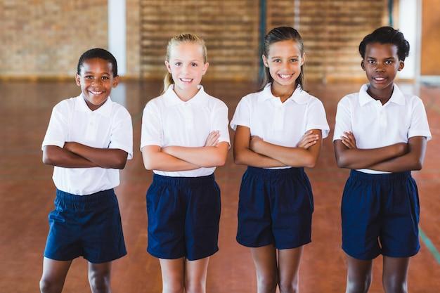 Portret van multi-etnische schoolkinderen permanent met gekruiste armen
