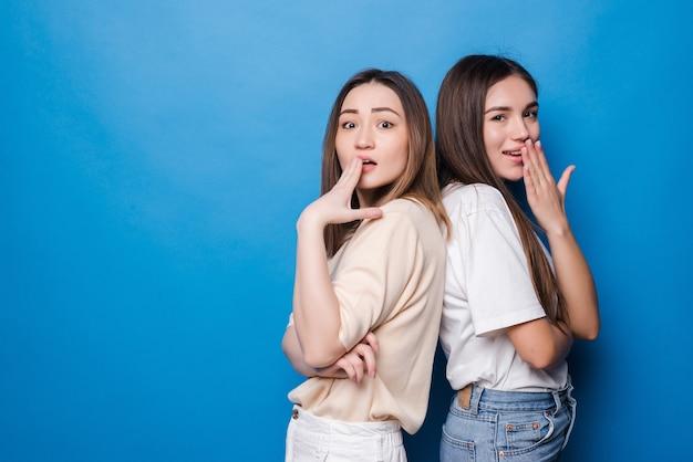 Portret van multinationale opgewonden vrouwen in vrijetijdskleding die en hun mond glimlachen bedekken die over blauwe muur wordt geïsoleerd