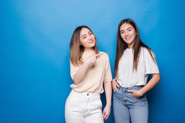 Portret van multinationale vrolijke vrouwen in vrijetijdskleding die en naar elkaar glimlachen wijzen geïsoleerd over blauwe muur