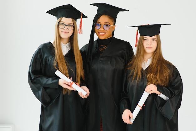 Portret van multiraciale afgestudeerden met diploma