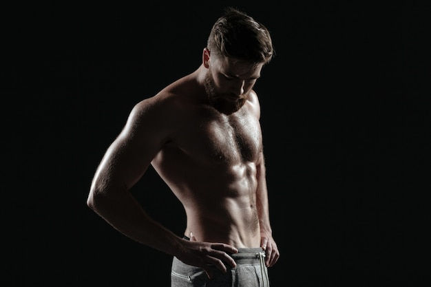 Portret van naakte atletische man. geïsoleerde donkere achtergrond