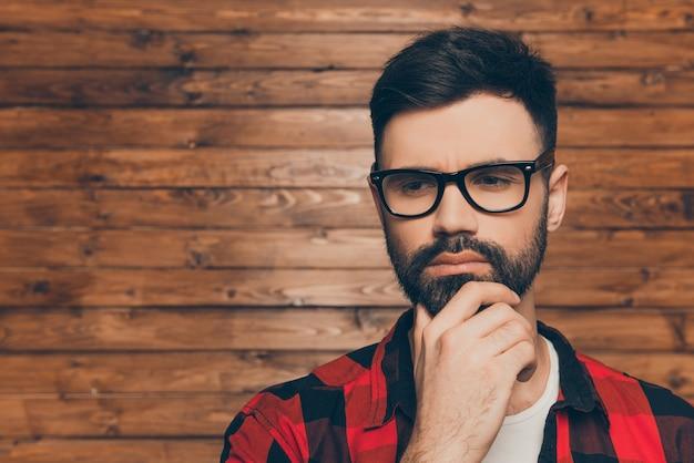 Portret van nadenken jonge man in glazen op houten muur