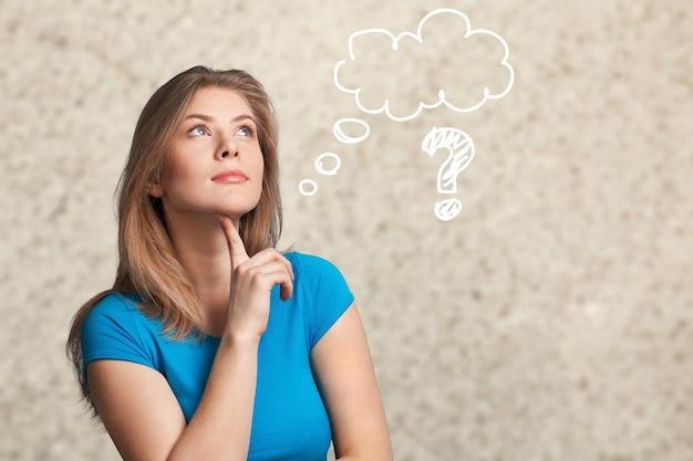 Portret van nadenkende jonge vrouw op grijze achtergrond met vraagteken