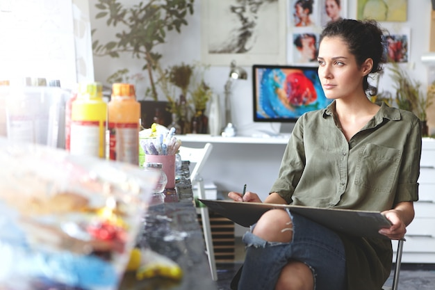 Portret van nadenkende mooie jonge donkerbruine vrouwelijke kunstenaar die kaki overhemd dragen en gescheurde jeans die op stoel thuis workshop zitten