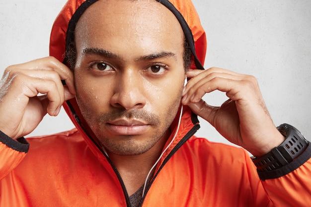 Portret van natte knappe jongen houdt hand op oortelefoons close-up, luistert luide audio