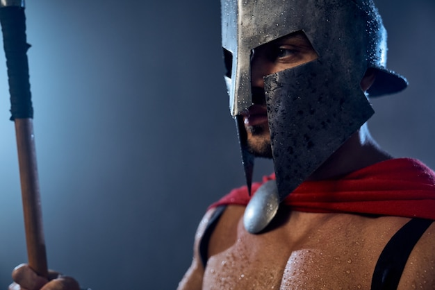 Portret van natte spartaanse krijger die speer vasthoudt en wegkijkt. close up van gespierde man in rode mantel en helm met waterdruppels poseren in donkere sfeer. oud sparta, krijgersconcept.