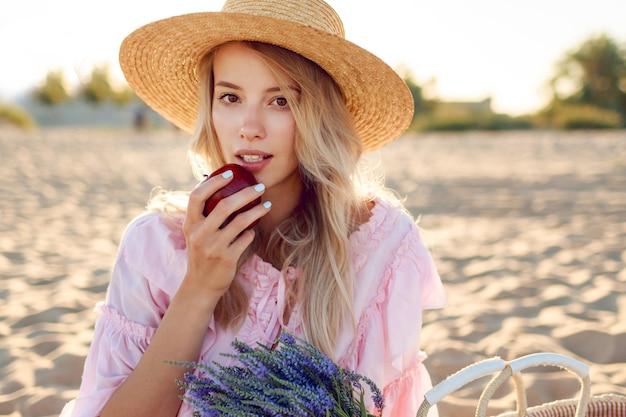 Portret van natuurlijk wit meisje in strooien hoed close-up genieten van weekends in de buurt van de oceaan. poseren met fruit. boeket van lavendel in strozak.
