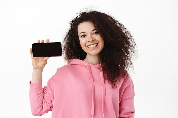 Portret van natuurlijke glimlachende krullende vrouw met smartphone