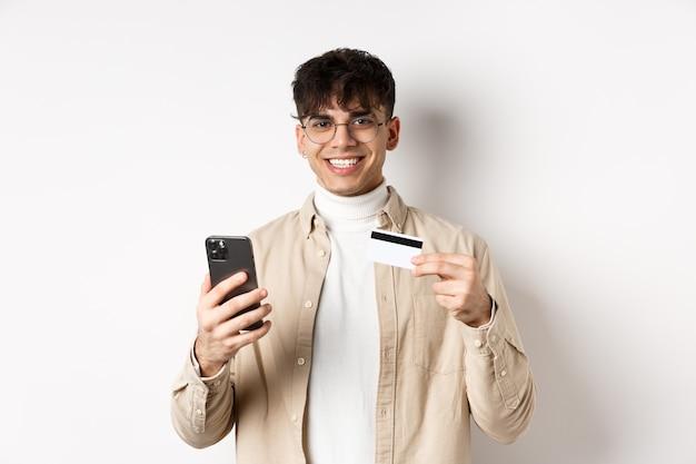 Portret van natuurlijke jonge man in glazen betalen op internet, smartphone en plastic creditcard tonen, staande op een witte muur.