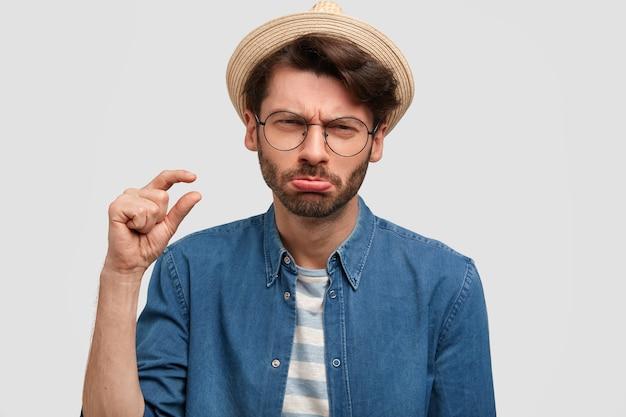 Portret van nauwgezette bebaarde jonge man toont iets heel kleins met de hand