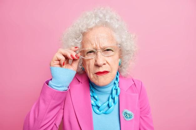 Portret van nauwgezette oma heeft een aandachtige blik, slecht zicht houdt de hand op de rand van een bril gekleed in modieuze kleding geeft altijd om haar uiterlijk poses binnenshuis. oude stijl concept