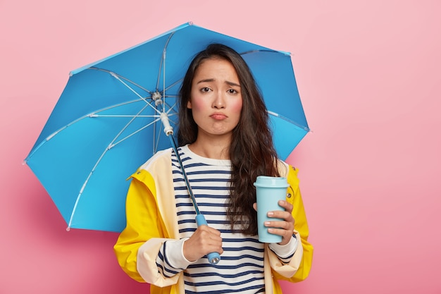 Portret van neerslachtige vrouw met koreaans uiterlijk, verdrietig vanwege slecht weer, voorspelling klopte niet, draagt blauwe paraplu, draagt regenjas