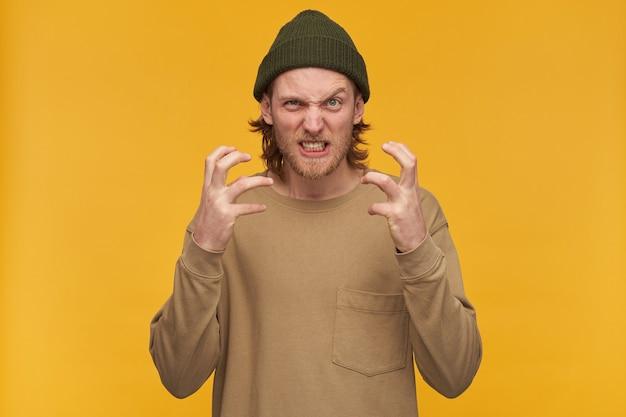 Portret van negatieve, geïrriteerde man met blond kapsel en baard. het dragen van een groene muts en een beige trui. woedend zijn gezicht van woede. geïsoleerd over gele muur