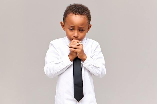 Portret van nerveuze gefrustreerde trieste afro-amerikaanse schooljongen in uniform neerkijkt met bezorgde gezichtsuitdrukking, knagende nagels, bang om te worden verteld voor slechte cijfers op school. oprechte emoties
